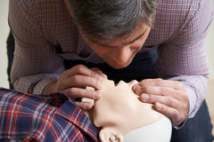 Man In First Aid Class Performing Mouth To Mouth Resuscitation O Royalty Free Stock Images