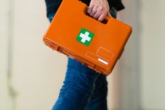Man with first aid kit runs to help. Work safety royalty free stock photography