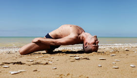Man in fish yoga pose Stock Image