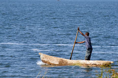 Man in fisher boat. SAMFYA, ZAMBIA - JUNE 29, 2014: An unidentified man stands in the fisher boat and rows at Lake Banguela Stock Photos