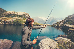 Man Fisherman fishing with rod alone. Lake and mountains landscape on background Lifestyle Travel survival concept Royalty Free Stock Image