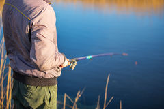 Man fisherman. Holding a fishing rod Stock Images