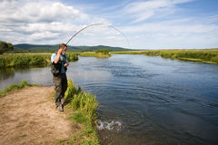 Man fishes caught salmon from the river Royalty Free Stock Photos