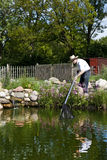 Man fishes in garden pond Royalty Free Stock Photo