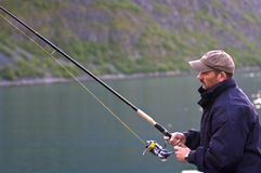 Man fishing. A man holding a fishing pole as he fishes in a Norwegian fjord Stock Images