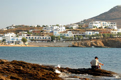 Man fishing. A man fishing in the greek islands with typical architecture in the background Stock Photos