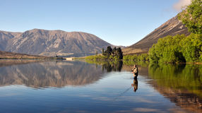 Man Fishing. In New Zealand in a lake near Arthurs Pass South Island New Zealand Stock Photos