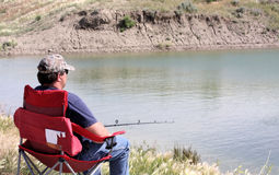 Man Fishing. Man sitting in a red chair fishing near the edge of a pond royalty free stock photos