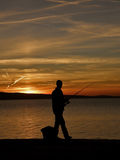 Man fishing. Alone man with fishing rod in a majestic - golden sunset at old pier (cleat - mooring detail) on the Adriatic Sea. Vertical color photo Royalty Free Stock Photography