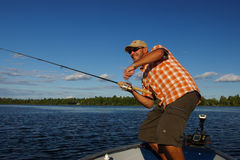 Man Fishing Large Mouth Bass. An action shot of a man fishing from a boat with rod and reel in hand Royalty Free Stock Photo