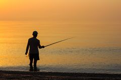 Man Fishing in the Sea at Sunrise Royalty Free Stock Image
