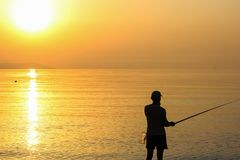 Man Fishing in the Sea at Sunrise Royalty Free Stock Photography