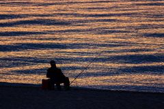 Man Fishing Alone in the Sea at Sunrise or Sunset Royalty Free Stock Images