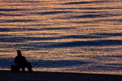 Man Fishing Alone in the Sea at Sunrise or Sunset Royalty Free Stock Photos