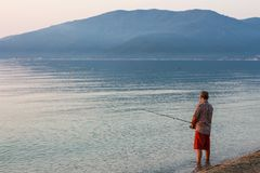 Man Fishing Alone in the Sea Very Early in the Morning - at Sunr Stock Photos