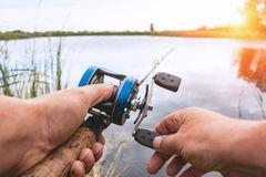 Man is fishing with a backcasting reel. A man is fishing with a backcasting reel. Hands, a rod and a backcasting reel in the background of the rising sun Royalty Free Stock Images