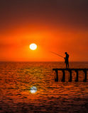 Man Fishing Background, Fishermen, Lake. Background illustration of a man fishing on a pier by a lake, sea, or ocean. The fisherman is enjoying the sunrise or Stock Photos