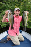 Man Fishing for Bass. A man in a colourful shirt poses for the camera with a largemouth and smallmouth bass Stock Photos