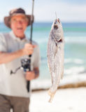 Man fishing at the beach. Man with a hat fishing at the beach Royalty Free Stock Photography