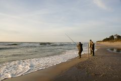 Man fishing on beach stock images