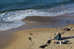 Man fishing from the beach Royalty Free Stock Photography