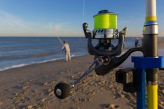 Man fishing on beach and close up of fishing rod royalty free stock images