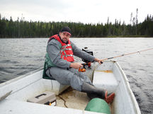 Man fishing. From a boat on a Northern lake Royalty Free Stock Image