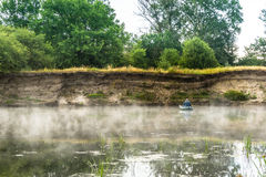 A man is fishing from a boat on the river. Morning landscape with mist over the river Royalty Free Stock Photography
