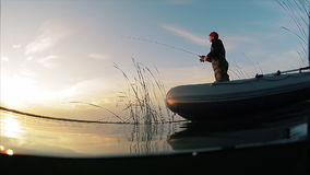 Man fishing from the boat. Split shot with underwater view stock video footage
