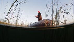 Man fishing from the boat. Split shot with underwater view stock footage