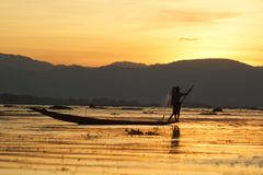 Man fishing on boat after sunset on Inle lake in Burma stock image