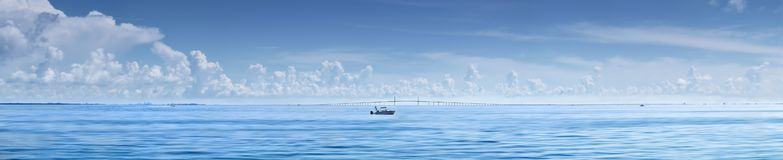 Fishing boat in front of Sunshine Skyway. Man fishing from boat with Sunshine Skyway Bridge,Florida in Background stock photo