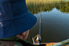 A man is fishing from a boat. View from behind the shoulder of a man, you can see the fishing rod and the float Stock Photo
