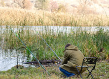 Man fishing at bthe side of a tranquil lake Stock Image