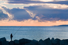 Man fishing  with calm sea and stormy clouds at dusk. Silhouette of a man with fishing rod alone on the rocks at dusk with calm sea and storm clouds Stock Image