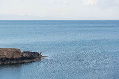 Man fishing from a cape. Man fishing from a rocky cape Royalty Free Stock Photo