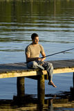 Man fishing on a dock Stock Image