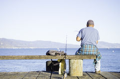 Man fishing on dock. A man sitting on a bench and fishing off of a dock into the ocean stock images