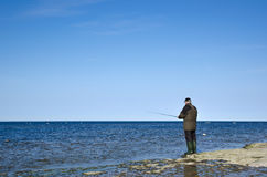 Man fishing at a flat rock coast Stock Images