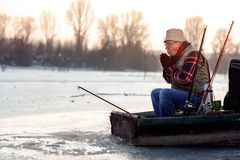 Man fishing on the frozen river in winter. Elderly man fishing on the frozen river in winter stock image