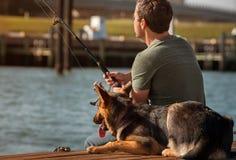 Man fishing. A man fishing with his dog Stock Photo