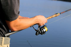 Man fishing. And holds the angling rod Royalty Free Stock Photos