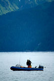 Man Fishing on Inflatable Boat in Alaska. A man fishes from a small inflatable boat off the coast of Seward, Alaska Royalty Free Stock Image