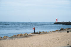 Man fishing infront of lighthouse Stock Photos