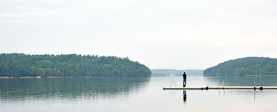 Man fishing from jetty Stock Photography