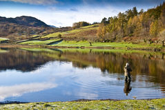 Man fishing in lake. Man fly fishing in lake district, cumbria with mountains reflected in lake Royalty Free Stock Photo