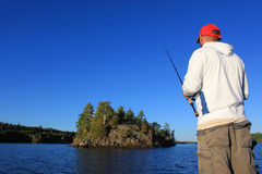 Man Fishing Large Mouth Bass. A man fishes from a boat on a lake, with an island and deep blue sky in the background Stock Photo