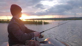 Man fishing on the lake. From the boat at sunset stock video