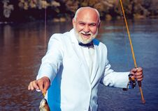 Man fishing on the lake. With fish. Summer vacation. Retired mature bearded male human in suit. Brutal man stand in