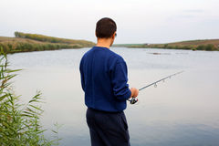 Man fishing in lake. Man holding fishing rod, casting rod in lake Royalty Free Stock Photography